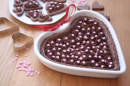 Dark chocolate tart in shape of a heart with a plate of decorated cookies on wooden table with decorations. Valentines day background