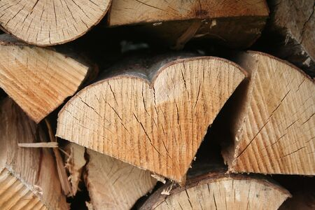 Stack of firewood with a tree log in shape of a heart. Wooden background