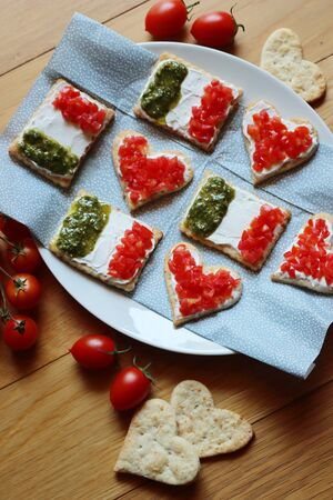 Salad cookies in shape of red heart and Italian flag on a plate on wooden table. Snack with tradional italian ingredient: pesto, cheese and red tomatoes Фото со стока