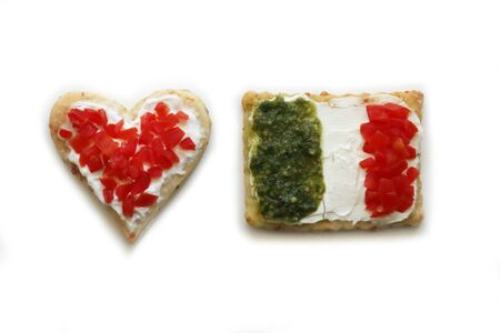 Salad cookies in shape of red heart and italian flag isolated on white background. Snack with tradional italian ingredient: pesto, cheese and red tomatoes