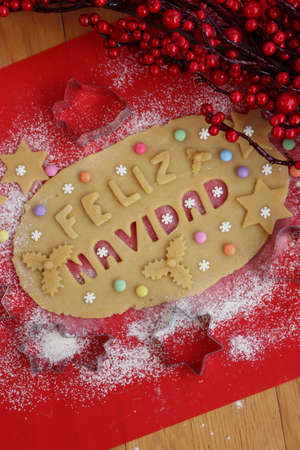 Feliz Navidad.Cookie dough letters on wooden table with sugar snowflakes and colorful chocolate candies with Christmas decoration