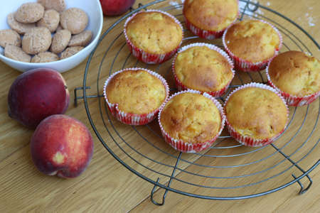 Muffins on a wire rack with peaches and italian Amaretti cookies on wooden table
