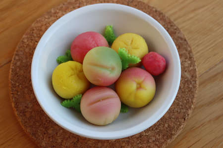 Traditional Italian Marzipan fruits in a bowl on wooden table. Sweet Marzipan shaped like fruits from Sicily