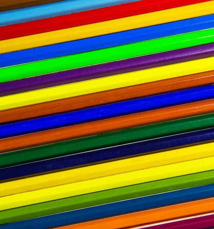 Colored wooden pencils of different colors in the background