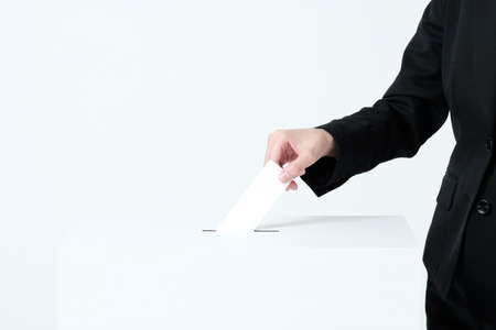 A woman's hand in a suit putting paper in an election ballot box 版權商用圖片
