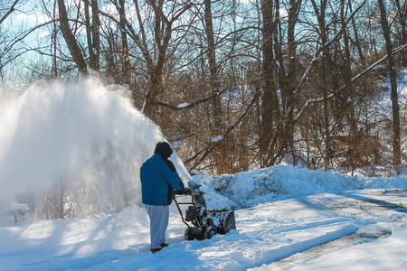 Adult male snow blowing his driveway after a snowfall