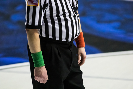 Male wrestling referee wearing red and green wrist bands and black and white striped shirt.