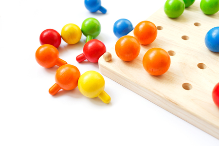 Colored pegs board, wood beads on white background Stock Photo