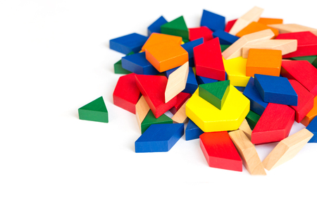 Multicolored pattern blocks on a white wooden background.Isolate.