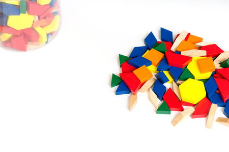 Multicolored pattern blocks on a white wooden background.Box with colored cubes.Isolate. Stock Photo