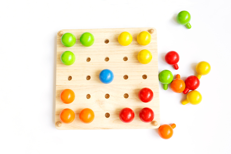Colored pegs board, wood beads on white background Stok Fotoğraf