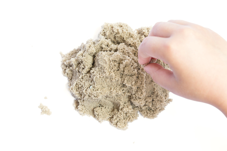 Child playing with kinetic sand. Hand of the child in the sand close up on a bright background Stock Photo
