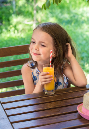 Little happy girl drinking orange juice from a glass in a cafe on a grassy background