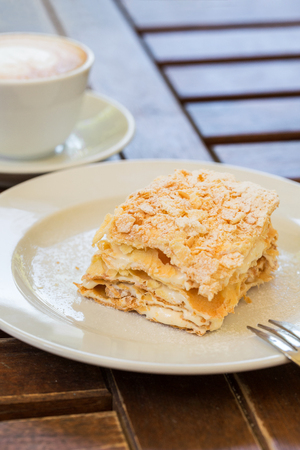 Napoleon cake, cappuccino coffee on the wooden table on the veranda in the cafe, in the garden Stock Photo