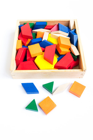 Wooden multi-colored blocks in a wooden box on a white background Stock Photo
