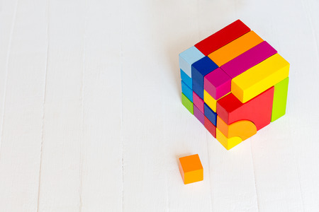 Colored wooden blocks, cubes, build on a light wooden background.A cube of colored wooden details