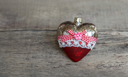 Glass Christmas toy on a wooden background. A heart.