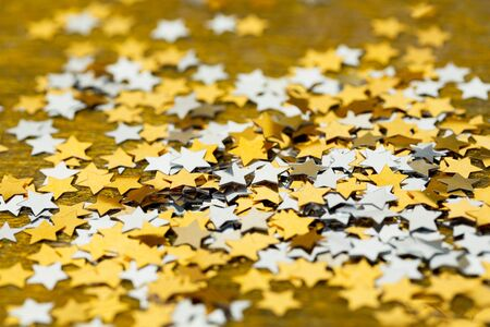 Asterisks shiny Christmas scattered on a gold background Stock Photo