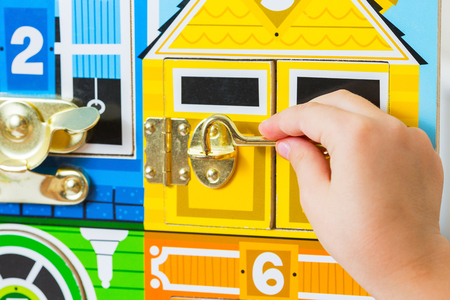 A game with locks. The child opens the locks. Busy-board for For children. Childrens educational toys.