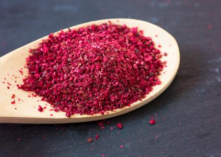 Spice Sumach on wooden spoon. Dark stone background 版權商用圖片