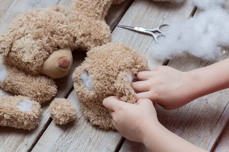A girl sews a bear toy. Handicraft with children. Child fills the toy with a sintepon.