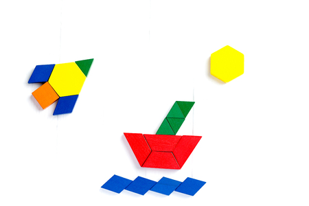 The ship sails on the sea waves, the sun shines brightly. Summer happy atmosphere. A child plays with colored blocks constructs a model on a light wooden background. Banco de Imagens