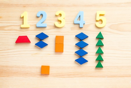 The child is studying the numbers and the account. Arranges the colored blocks to the desired numbers. Mathematics for children Stock Photo