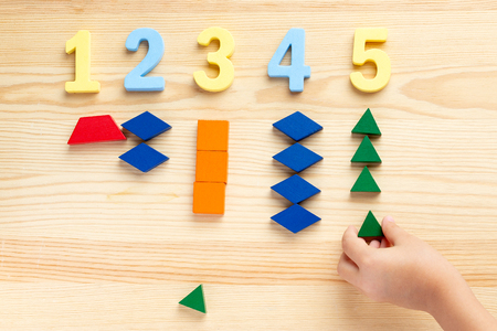 The child is studying the numbers and the account. Arranges the colored blocks to the desired numbers. Mathematics for children Reklamní fotografie