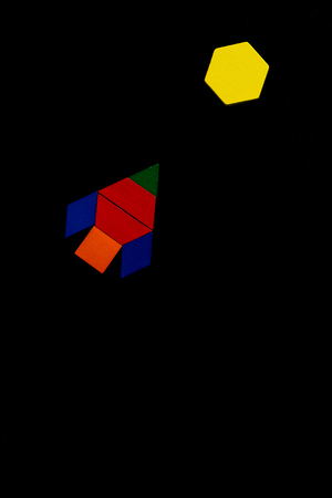 The space ship flies into space to another new planet. Summer happy atmosphere. A child plays with colored blocks constructs a model on a black background Stock Photo