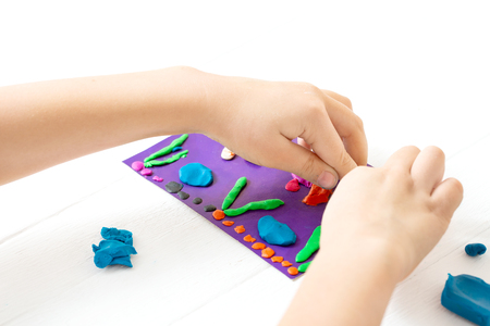 A child kneads plasticine and sculpts an aquarium with fish. Tutoring with children.