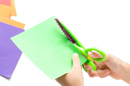 Childrens hands cut out colored paper with figured scissors. Activities for children, leisure.