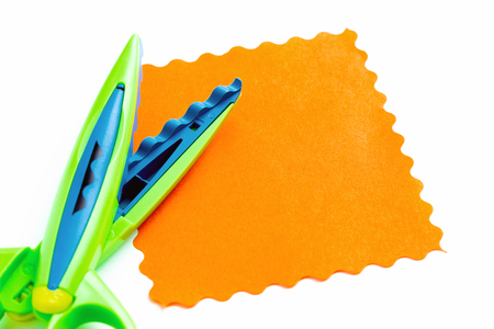A sheet of orange paper with a wavy edge lies on a white background near the curly scissors. Creativity, playing with children at home and in kindergarten
