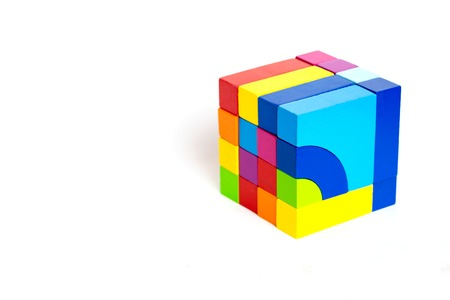 Colored wooden blocks, cubes, build on a light white background. A cube of colored wooden details