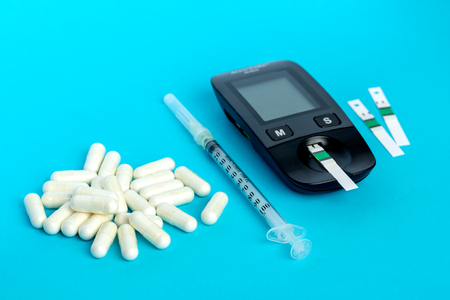 Glucometer, medication, syringe lie on a blue background