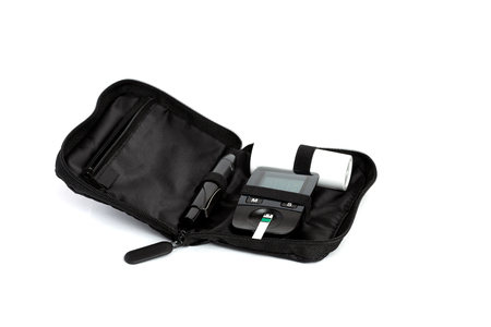 Glucometer and test strip lies in bag case on a white background Stock Photo