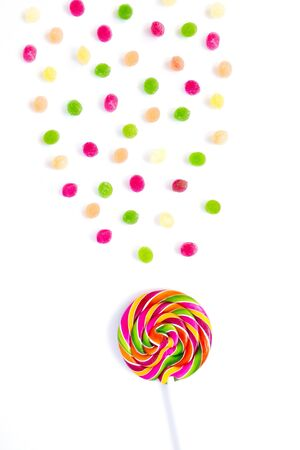 Rainbow sweet sweet bright round lollipop and many colorful little lollipops on a white background.