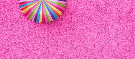 Rainbow colored paper baking cups for muffins and cupcakes on a pink background
