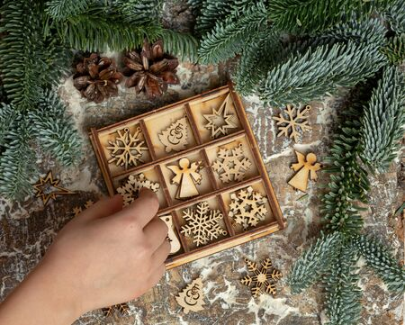 The hand of the child puts a wooden Christmas toy in a box. Stock fotó