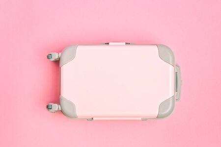 Pink suitcase on a pink background.