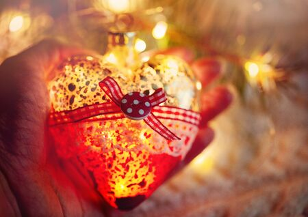 Female hand holds a glass heart, a Christmas toy - a garland in the hands on the background of a warm knitted sweater. Evening time.