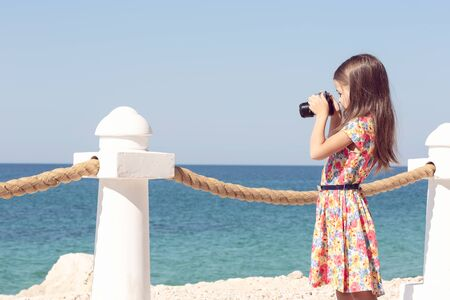 A girl photographs with a camera in a red dress against the sea