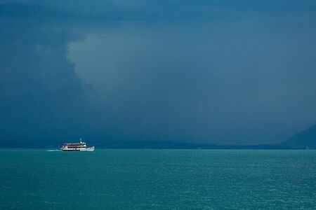 The view from the top to Lake Garda is fabulous. A gloomy sky awaiting a thunderstorm. Ship, boat, freshness, rain.