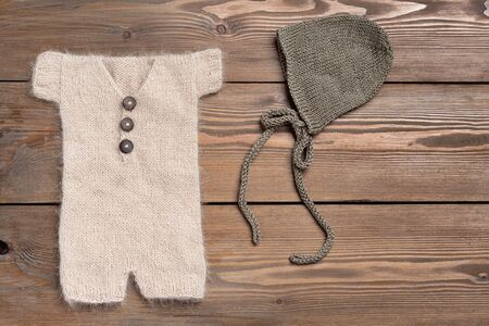 Set of Baby clothes for newborn brown, beige in wooden background. Body, Hat for newborn