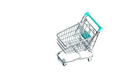 Miniature empty shopping cart turquoise color on white background. isolated. Top view, flat lay. Banco de Imagens