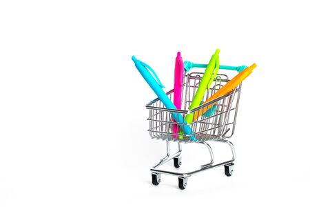 Miniature shopping cart turquoise color with colorful pens on white background. isolated Banco de Imagens - 132126551