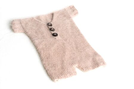 Baby clothes for newborn in brown, beige colors on white wool background. Set of baby clothes. Body for newborn.