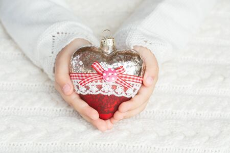 Child holds a glass heart, a Christmas toy in the hands on the background of a warm knitted sweater. Stock fotó