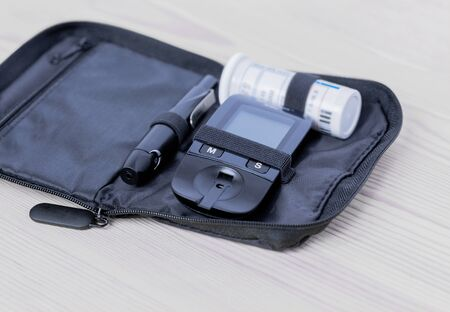 Glucometer, lanset and test strip lies in bag case on the wooden table on the left side. Concept of health, medicine.