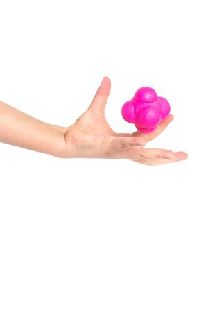 A child catches with one hand the magenta (pink) sports ball reaction on white background. Фото со стока