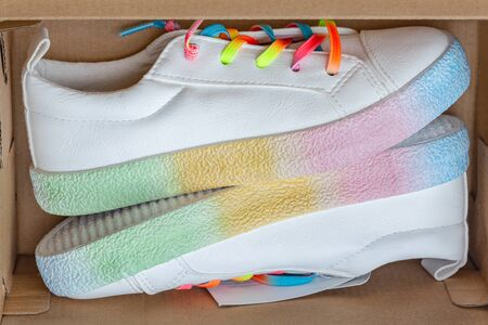 white sneakers with rainbow shoelaces are in a brown box